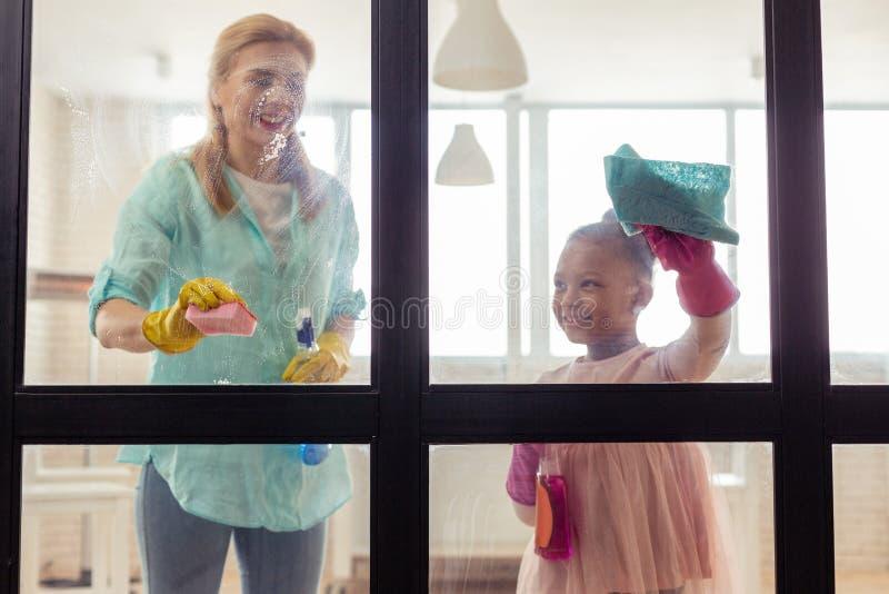 Mutter und Tochter, die zusammen Zeit beim Säubern der Wohnung verbringen stockfoto
