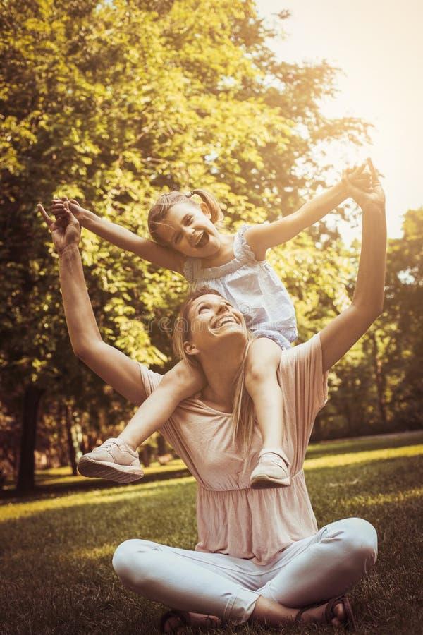 Mutter und Tochter draußen in einer Wiese Kleines Mädchen, das an sitzt stockfotografie