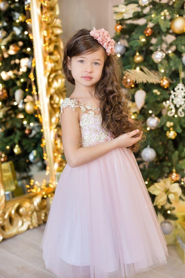 Mutter und Tochter feiern tragende Sankt-Hüte Nettes kleines Mädchen in einem schönen Kleid, das nahe dem Weihnachtsbaum sitzt We lizenzfreies stockfoto
