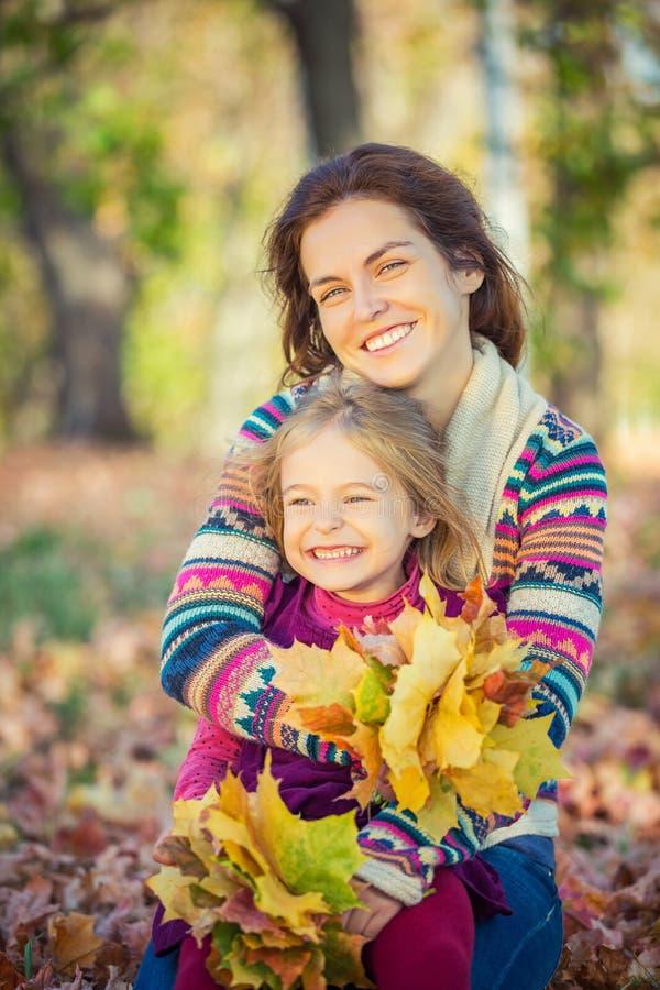 Mutter und Tochter genießen sonnigen Herbst im Park stockbild