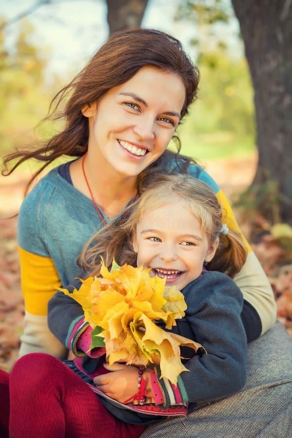 Mutter und Tochter genießen sonnigen Herbst im Park lizenzfreies stockfoto