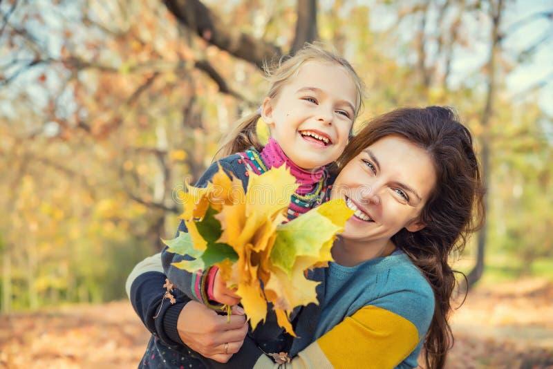 Mutter und Tochter genießen sonnigen Herbst im Park lizenzfreie stockfotos