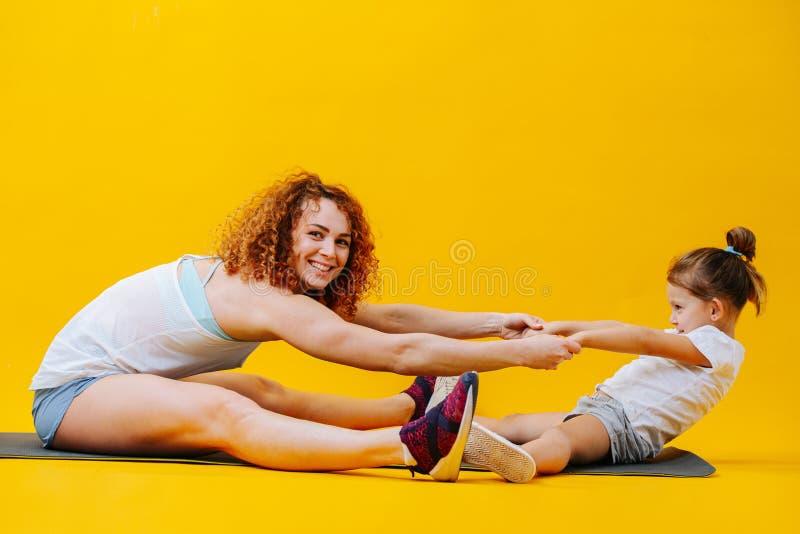 Mutter und Tochter helfen einander, sich über gelben Hintergrund zu strecken stockbild