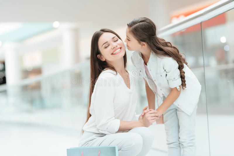 Mutter und Tochter im Einkaufszentrum Mädchen küsst Frau auf Backe lizenzfreies stockbild