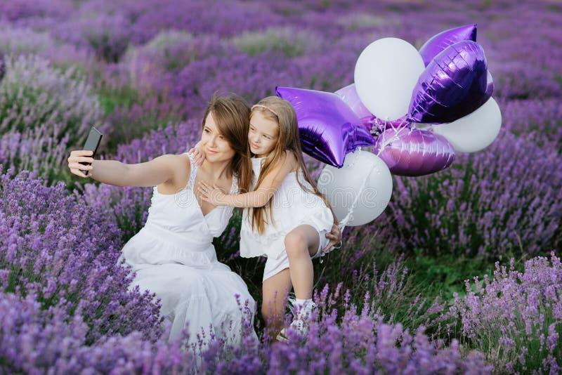 Mutter und Tochter machen selfie auf Smartphone auf dem Lavendelgebiet Ein reizendes Baumhaus, eine Vogelfamilie, eine Taste der  stockbild