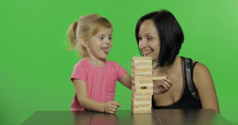 Mutter und Tochter spielt das jenga Kind zieht Holzklötze vom Turm lizenzfreie stockfotos