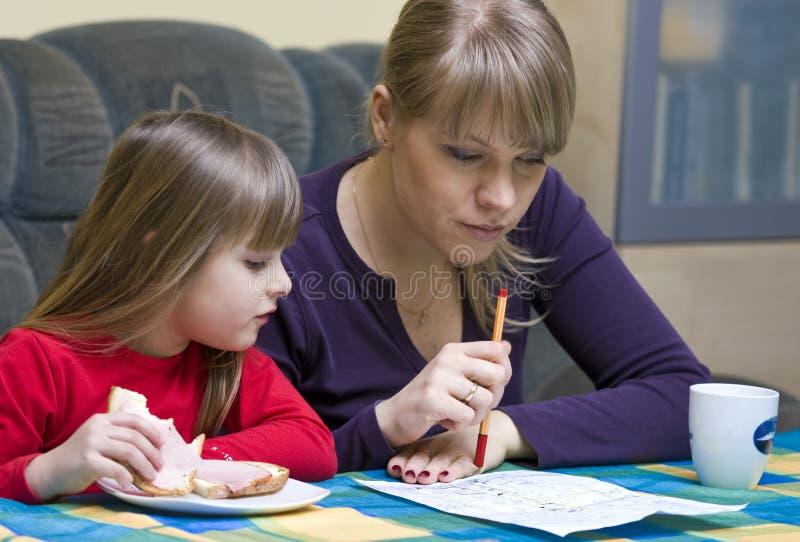 Mutter und Tochter am Tisch stockfotografie