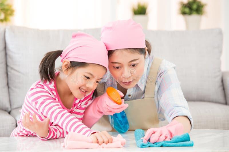 Mutter und Tochter tun das Reinigungshaus stockfoto