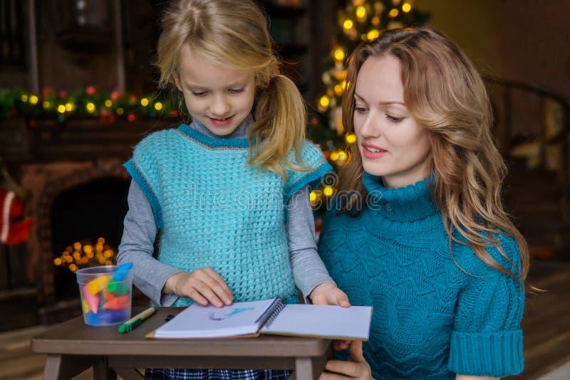 Mutter und Tochter verbringen Freizeit zusammen im Wohnzimmer am Weihnachtsbaum draw lizenzfreie stockfotos