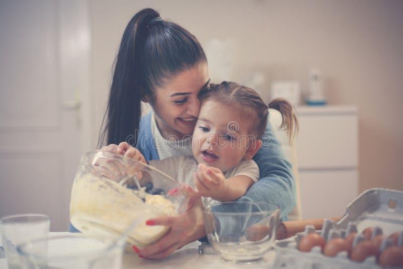 Mutter- und Tochterbackenplätzchen und mischender Teig stockbild