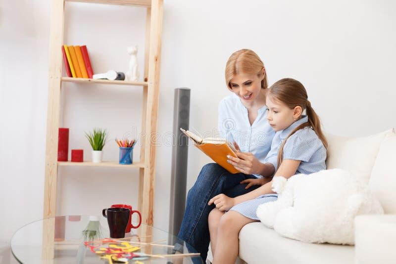 Mutter- und Tochterlesebuch zu Hause lizenzfreies stockbild