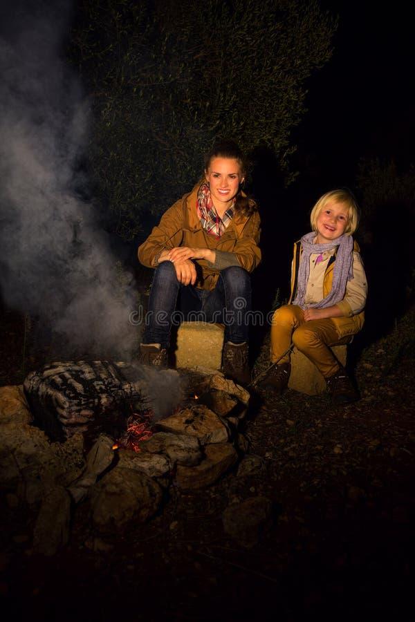Mutter- und Tochterreisende, die nahe kampierendem Feuer sitzen lizenzfreie stockfotografie
