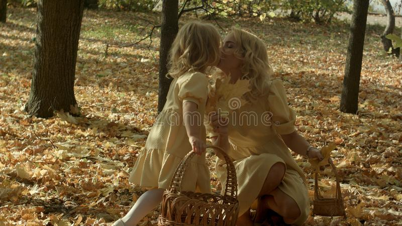 Mutter- und Tochterspiel im Herbstpark Elternteil und Kind gehen in den Wald an einem sonnigen Falltag Childs Spiel lizenzfreie stockfotografie