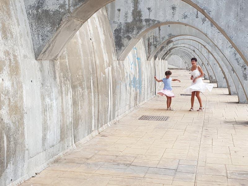Mutter- und Tochtertanzen unter den Bögen des Hafens von Mala stockfoto