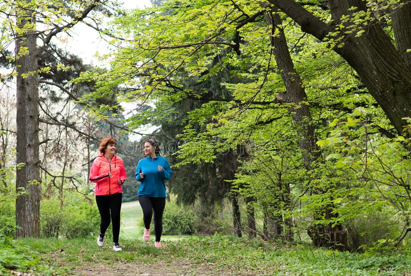 Mutter und tragende Sportkleidung und Betrieb der Tochter im Wald stockfotos