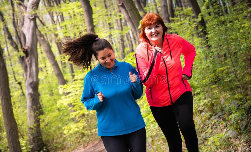 Mutter und tragende Sportkleidung und Betrieb der Tochter im Wald lizenzfreie stockbilder