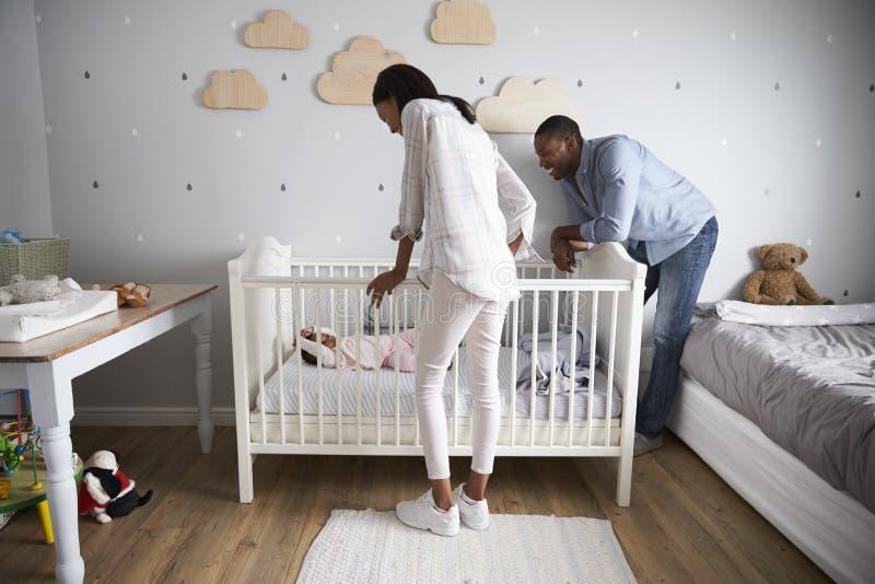 Mutter-und Vater-Looking At Baby-Tochter im Kindertagesstätten-Feldbett lizenzfreie stockbilder