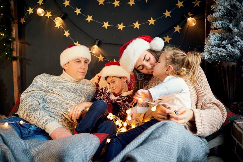 Mutter und Vater mit den Kindern, die zu Hause am Weihnachtstag spielen lizenzfreie stockfotos