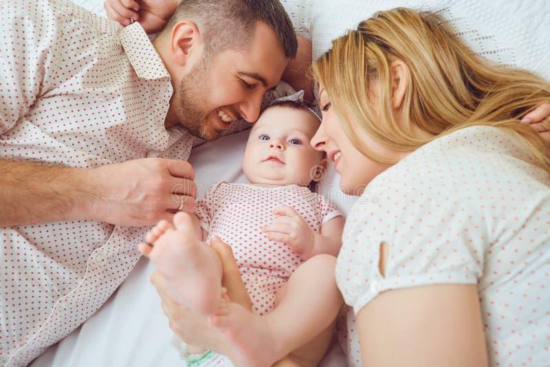 Mutter und Vater spielen mit dem Baby auf dem Bett stockbilder