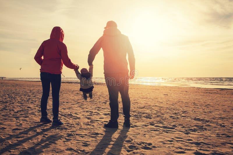 Mutter- und Vaterschwingkind durch die Arme auf dem Strand stockfoto