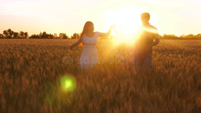 Mutter und Vati tragen kleine Tochter in den Armen über Feld des Weizens in den schönen Strahlen des Sonnenuntergangs Baby mit de lizenzfreie stockfotografie