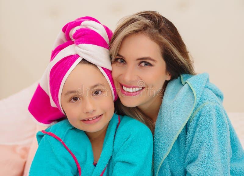 Mutter und wenig Tochtertragen, die blaue Bademäntel im Raum sind stockfotos