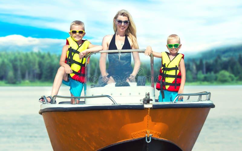 Mutter und zwei Söhne schwimmen auf einem Motorboot auf dem See stockfoto