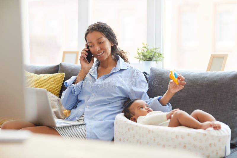 Mutter unter Verwendung der Lotterie für Baby bei der Unterhaltung mit Kunden am Telefon stockfotos