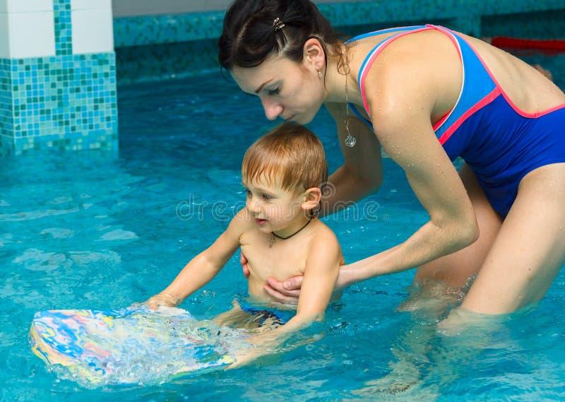 Mutter unterrichtet Baby zu schwimmen lizenzfreie stockfotografie