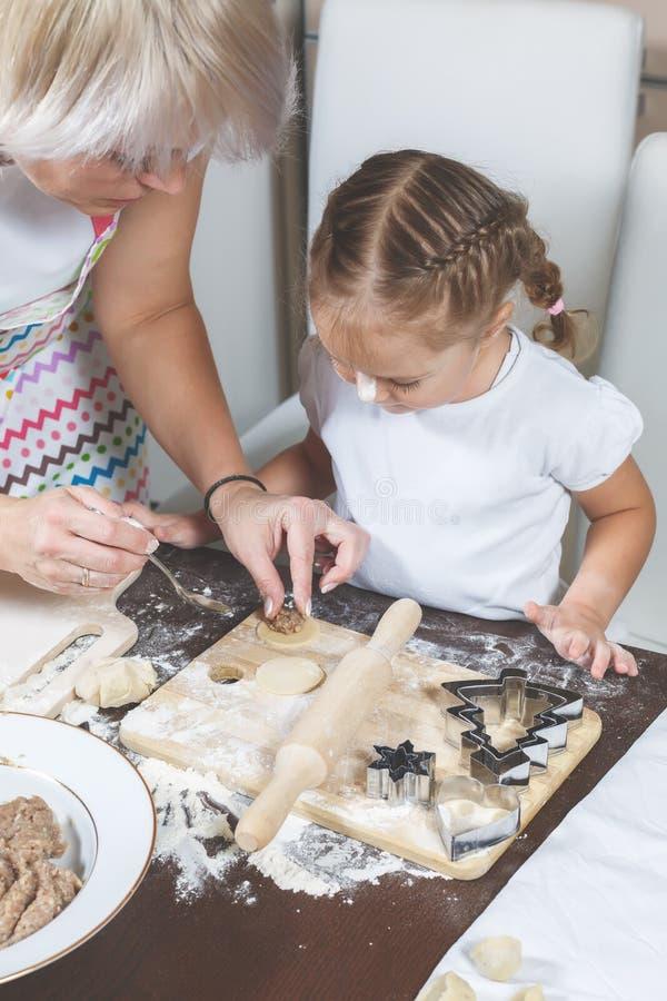 Mutter unterrichtet ein kleines Mädchen, Mehlklöße zu machen lizenzfreie stockfotografie
