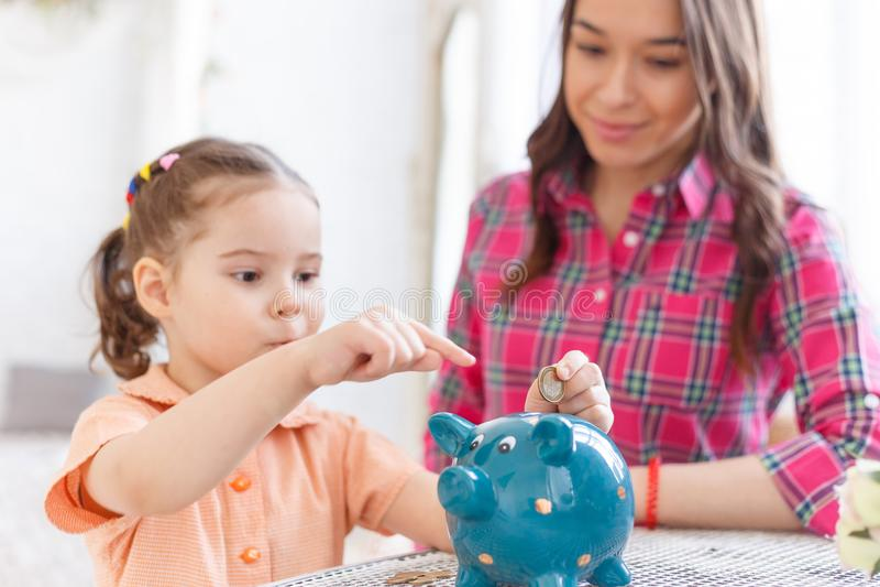 Mutter unterrichtet eine kleine Tochter, Geld in einem Sparschwein zu sammeln lizenzfreie stockfotografie