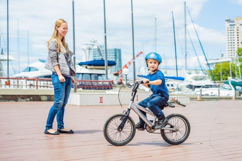 Mutter unterrichtet Sohn, ein Fahrrad im Park zu reiten stockbild