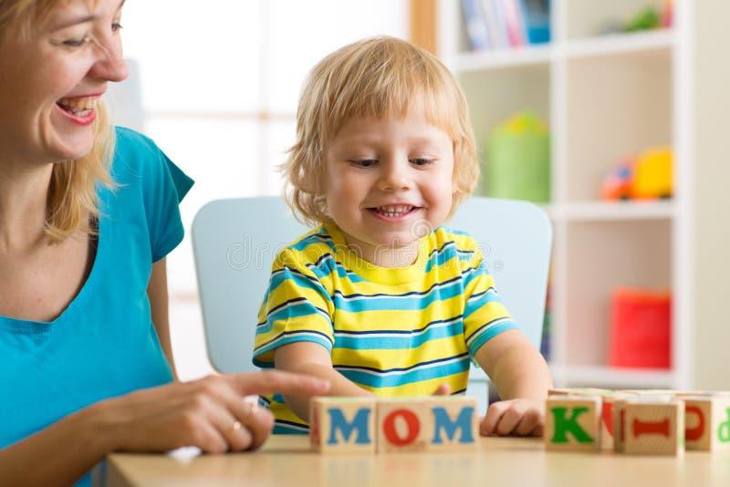 Mutter unterrichtet Sohnkind, die Briefe und Wörter zu lesen, die mit Würfeln spielen lizenzfreie stockbilder