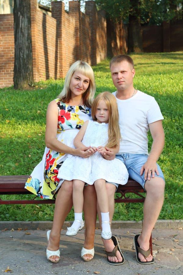 Mutter, Vater, kleine Tochter sitzen auf Bank in sonnigem p lizenzfreies stockbild