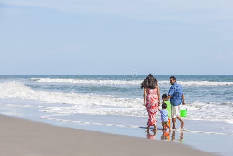 Mutter-Vater u. Kinderfamilie, die auf Strand geht stockfotografie