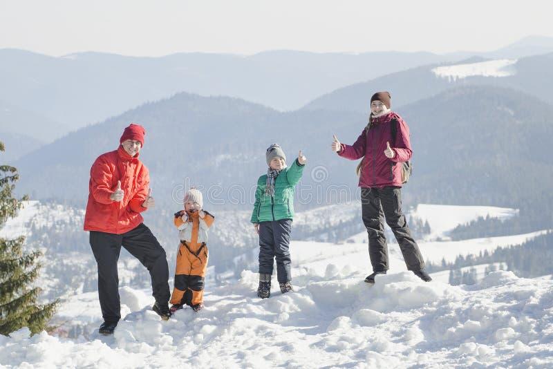 Mutter, Vater und zwei Söhne sind, lächelnd stehend und gegen den Hintergrund von Schnee-mit einer Kappe bedeckten Bergen Glückli stockbilder