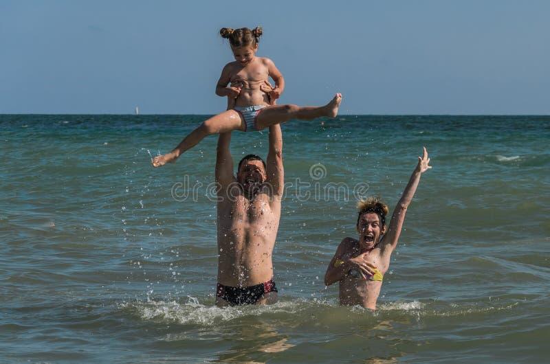 Mutter-, Vati- und Tochterschwimmen, spielt und hat Spaß in dem Meer im Erholungsort - eine glückliche Familie stockbild