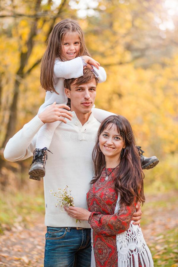 Mutter-, Vati- und Tochterweg durch die Herbstwaldtochter sitzt auf den Schultern des Vaters stockbilder