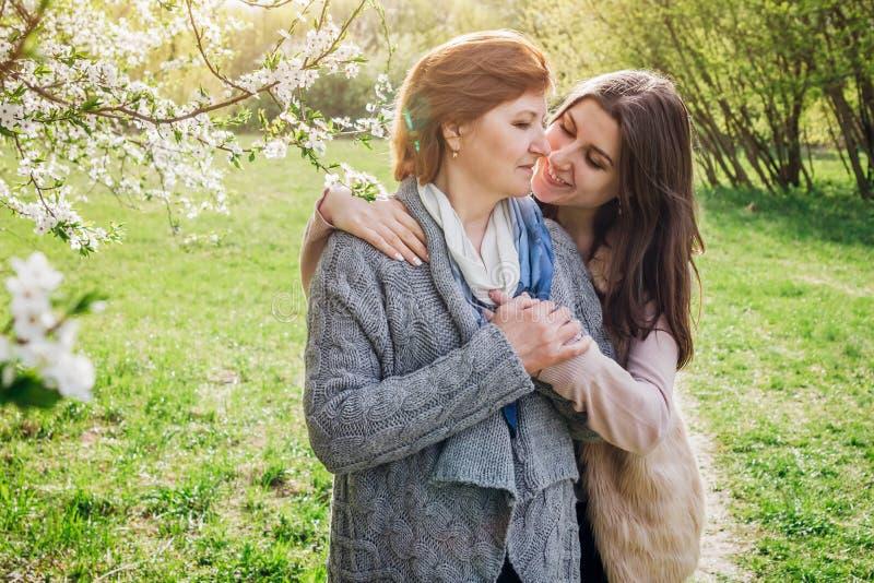 Mutter von mittlerem Alter und ihre Tochter, die in blühendem Garten umarmt stockfoto