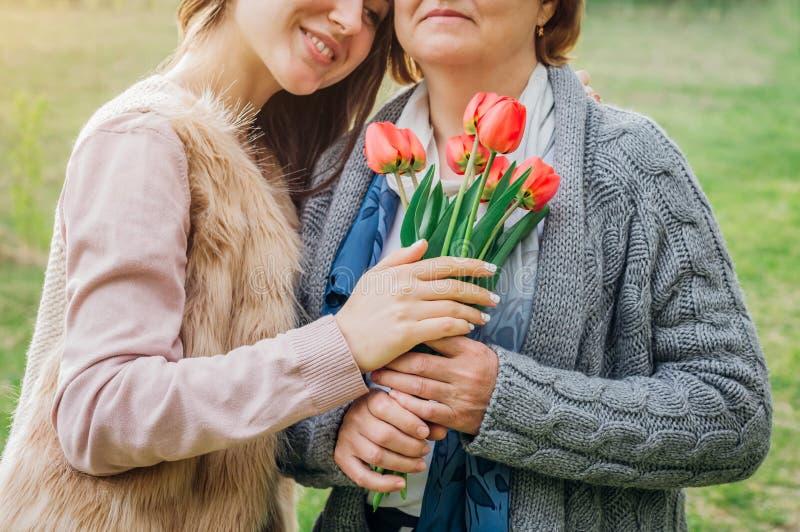 Mutter von mittlerem Alter und ihre Tochter, die in blühendem Garten umarmt lizenzfreie stockbilder