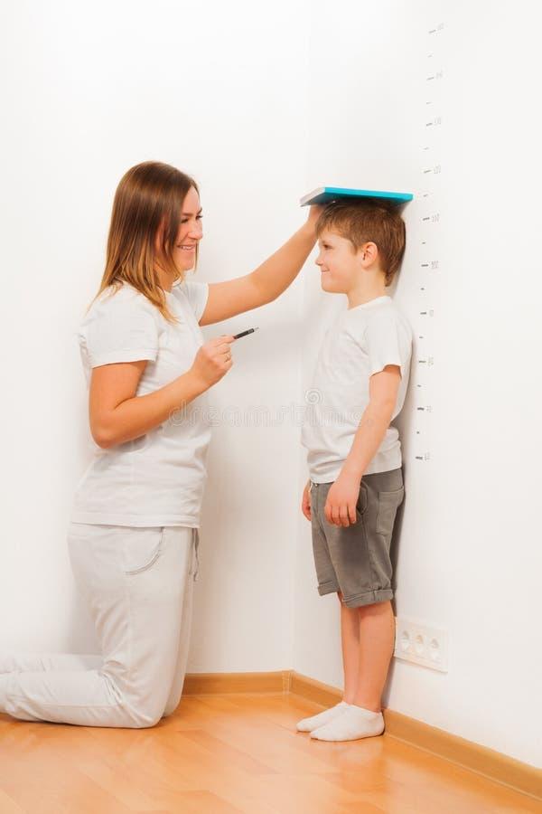 Mutter, welche die Höhe ihres Sohns auf Wachstumstabelle überprüft stockbild