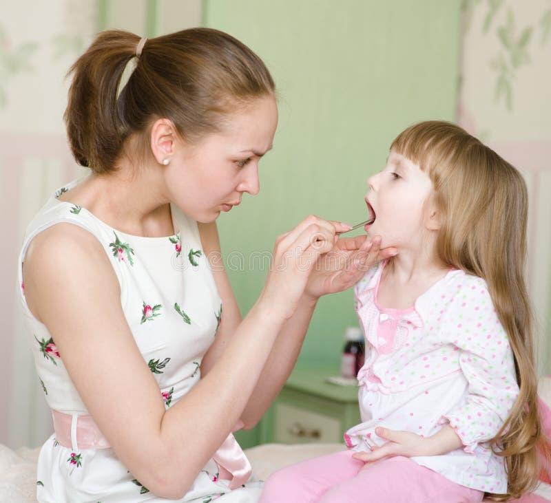 Mutter, welche die Kehle des kleinen Mädchens überprüft stockbild