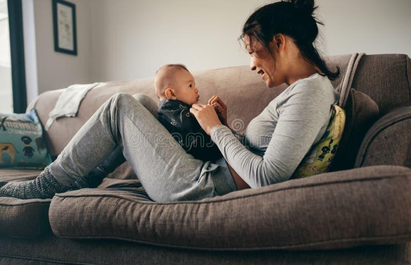 Mutter, welche die Zeit zu Hause spricht mit ihrem Baby verbringt lizenzfreie stockbilder