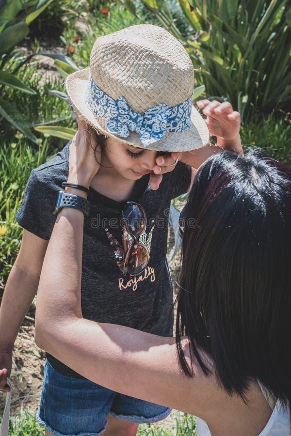 Mutter, welche weg die Risse des Kindes von ihrem Gesicht abwischt stockfoto