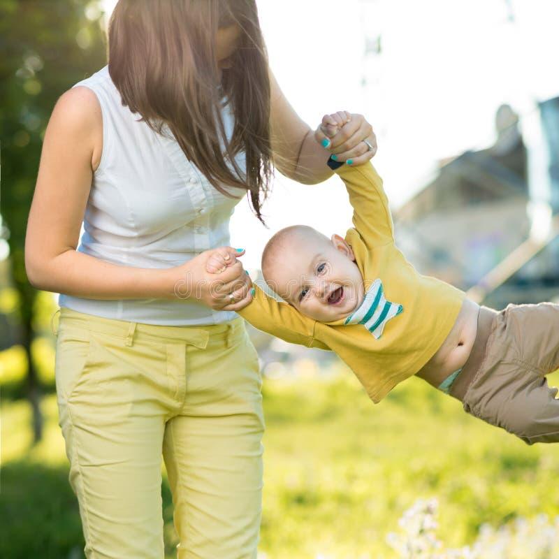 Mutter wirft Baby in ihren Armen oben lizenzfreies stockbild