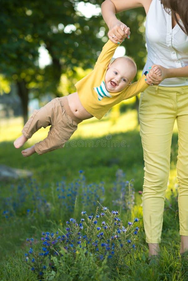 Mutter wirft Baby in ihren Armen oben stockbild