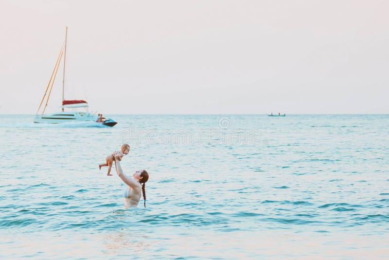 Mutter wirft oben Baby im Himmel im Wasser des Meeres Glückliche Familiensommerfreizeit mit Säuglingsmädchen Yacht und hydrocycle stockfotos