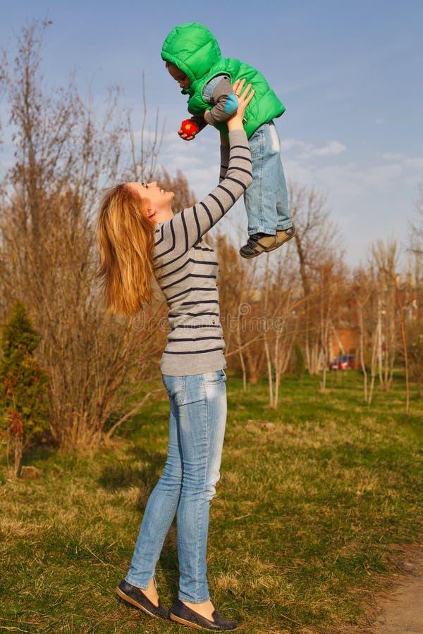 Mutter wirft oben ihren Sohn stockfotos