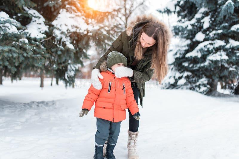Mutter wischt seinen Sohnjungenrotz mit einem Handschuh ab Interessieren für ein Baby mit einer verstopften Nase Im Winter im Par stockbild