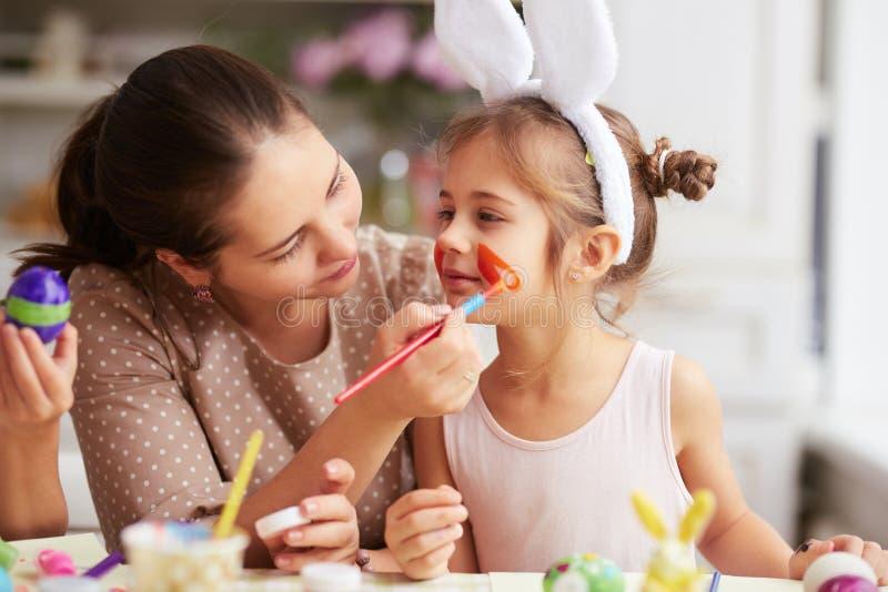 Mutter zeichnet auf das Gesicht der Tochter beim Färben der Eier für die Ostern-Tabelle in der gemütlichen hellen Küche stockbild